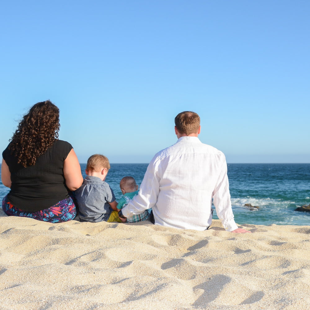 Family of Four from Behind Sitting on Beach in Sand