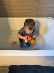 Toddler in Bath Tub in Clothes