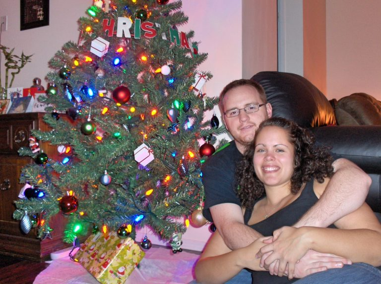 Young Couple in Front of Christmas Tree