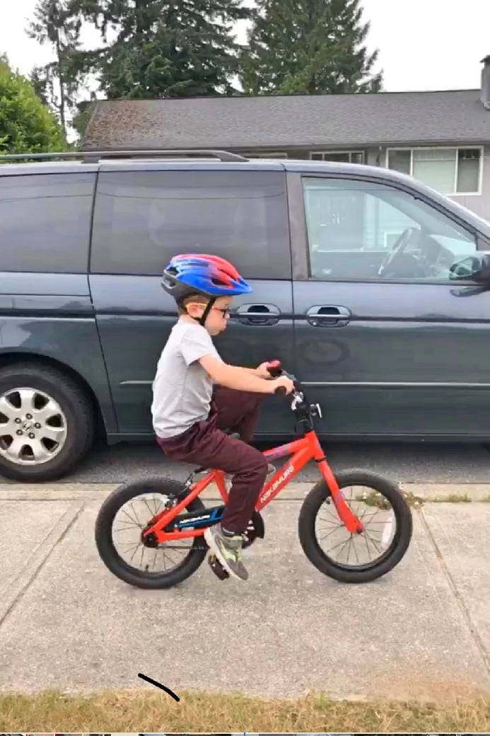 Boy on Bike with Tongue Out