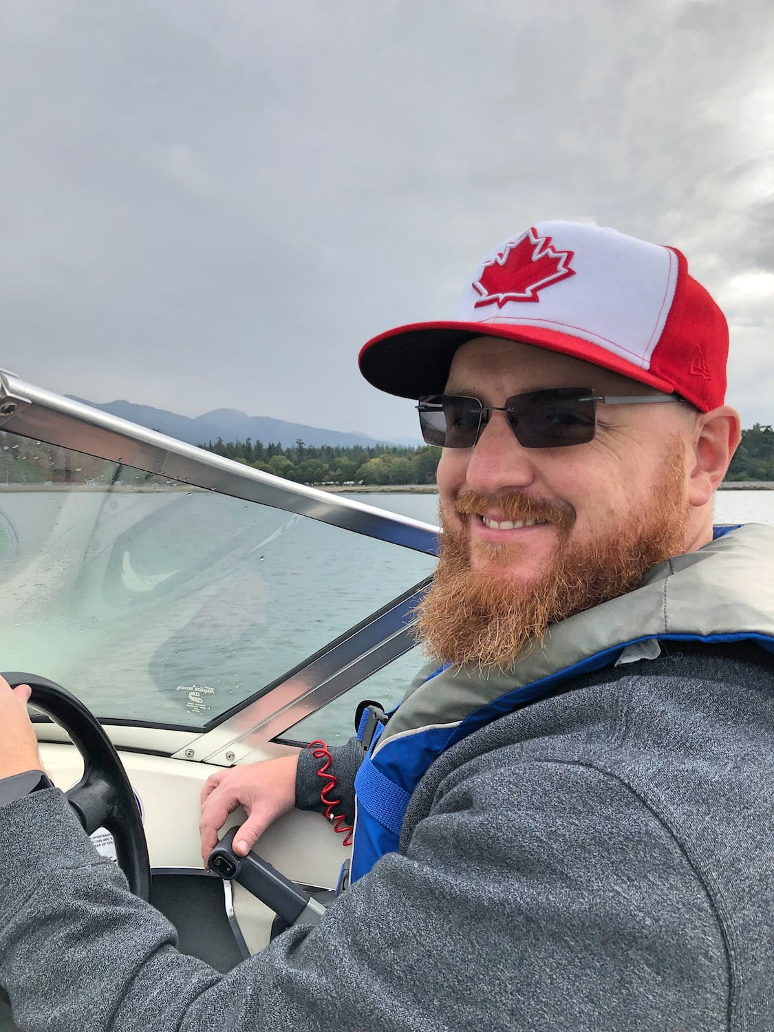 Captain Dad Driving Boat with Canadians Hat