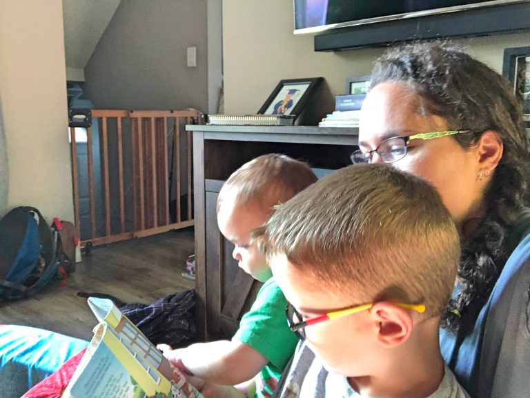 Mom reading to kids in lap