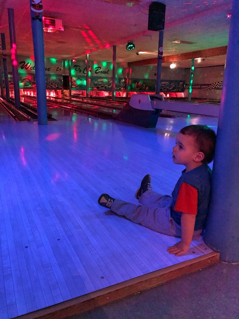 Toddler Sits at Edge of Bowling Alley