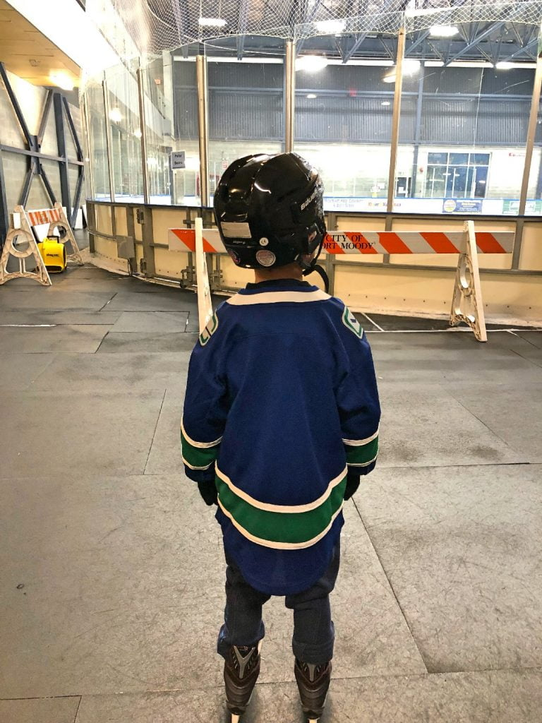 Boy Standing in Skates at Ice Rink