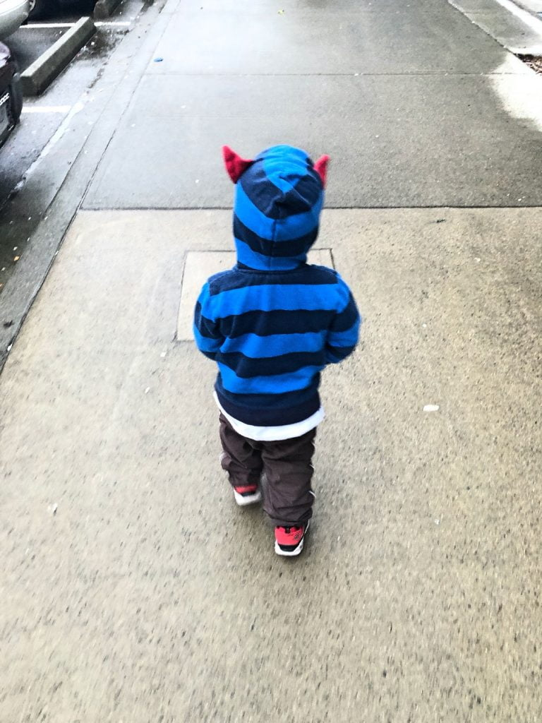 Toddler with Devil Horns on Sweater Walking Away