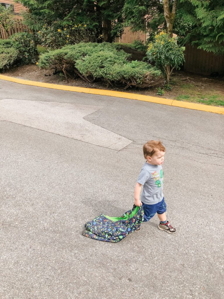 Toddler Walking Down Road Dragging Jacket