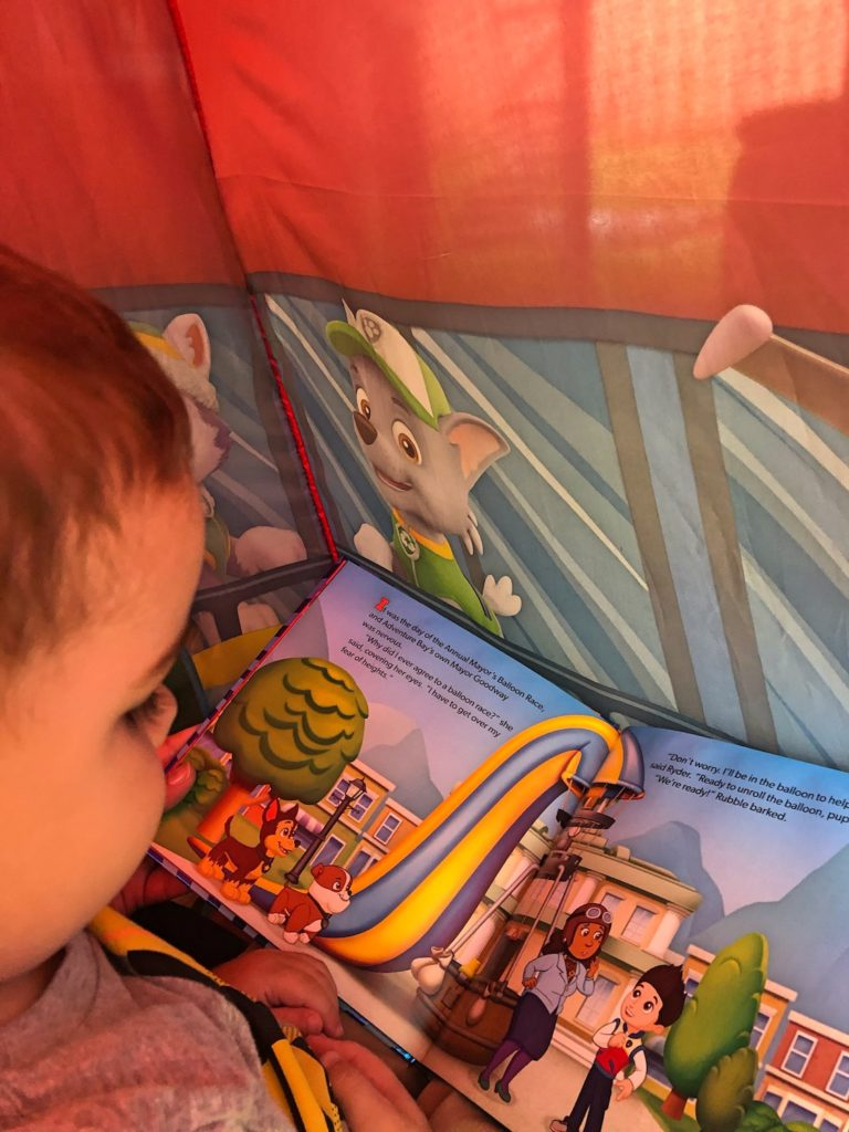 Child in Paw Patrol Play Tent Reading Paw Patrol Book