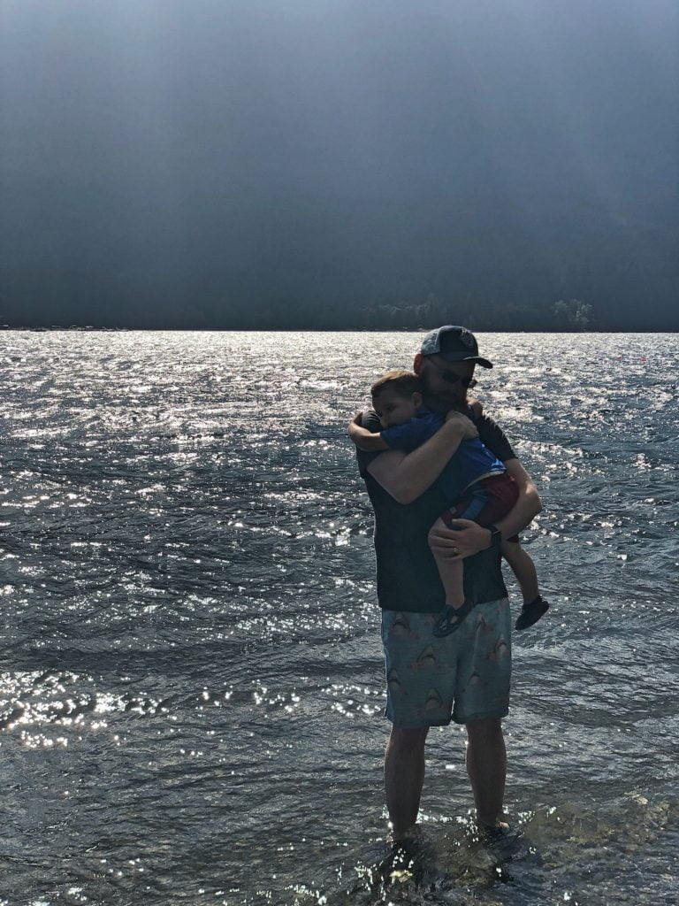 Father Snuggling Son while Standing in Lake