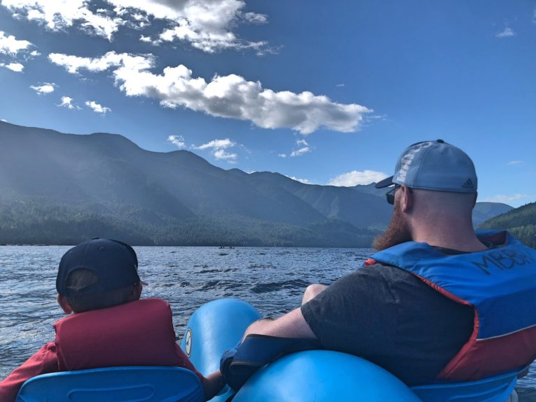 Father and Son from Behind in Pedal Boat with Blue Sky and Clouds