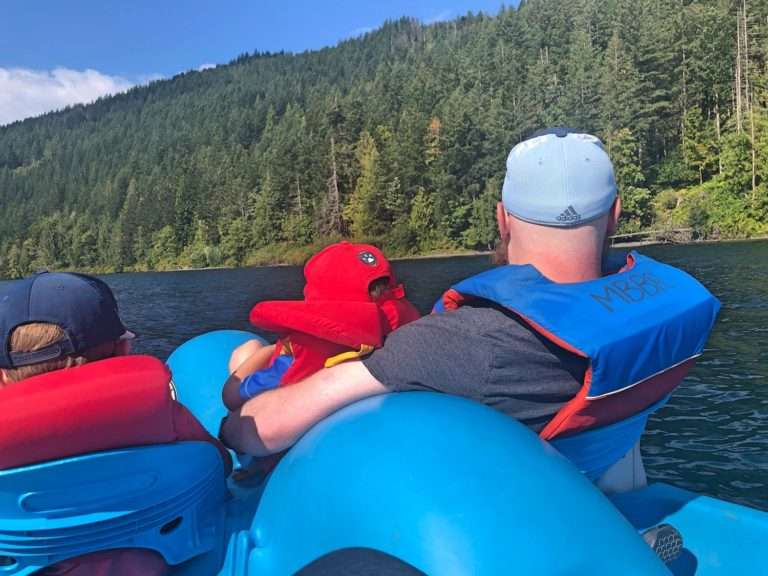 Father and Sons from Behind in Pedal Boat with Forest in Background