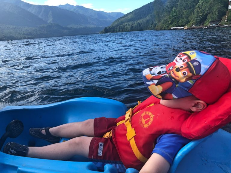 Toddler in Life Jacket Laying in Pedal Boat