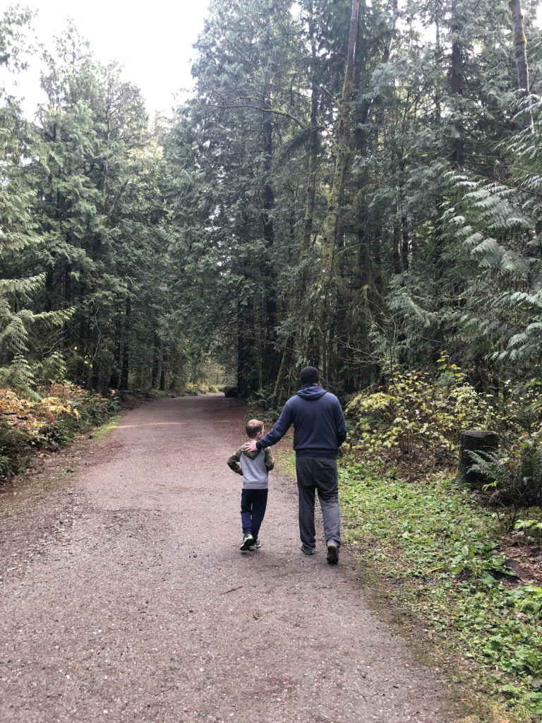 Father and Son Walking Down Forested Path at Mundy Park