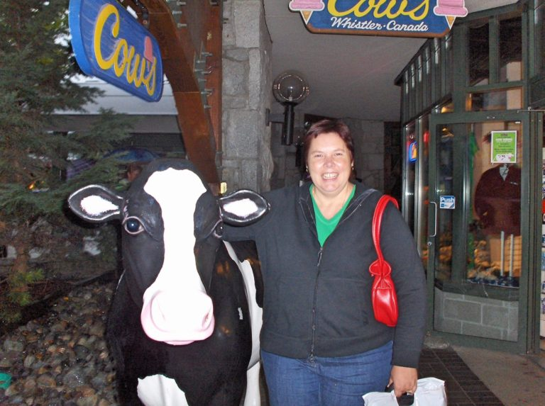 Woman Standing with Plastic Cow at Cows, Whistler (2007)