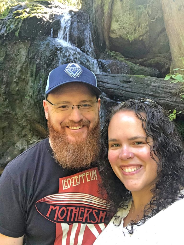 Red-Bearded Man and Curly-Haired Brunette Woman Smiling in Front of Waterfall